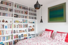 Beautiful white bedroom with cool wall encapsulating shelves. Bibliothèque fermée: by Lise Compain