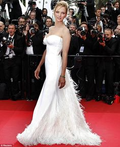 Uma Thurman rocked to the beat as she sashayed along the red carpet for the opening of the Cannes Film Festival tonight.    The actress looked stunning in a white silk Versace gown that up close appeared to be see-through.