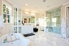 Marble flooring anchors this bright bathroom, featuring full height glass door cabinets next to a vanity with lower makeup space. Pedestal tub stands across from large glass enclosure shower.
