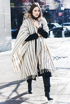 A black sweater is paired with a blanket poncho, black pants, and lucite-heel boots