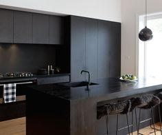 After completing a glossy white kitchen in their previous home, this Auckland family decided to go bold and created a seamless black kitchen for $40,000