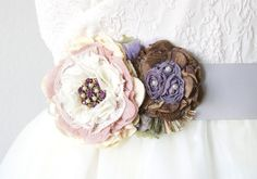 Description An unexpected and colorful addition to your wedding gown, this bridal sash features two beautiful handmade fabric blooms in lavender purple, chocolate brown and rosy pink hues. The sparkli
