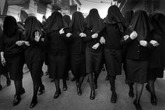 Holy Saturday, Puglia, Italy, 2000 by Cristina Garcia Rodero. Group of women marching on the streets and singing their grief at the death of Christ