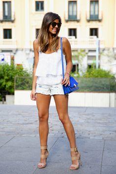 Top blanco con shorts vaqueros claros y toque de color en bolso y sandalias.