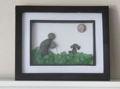 This creative dog and dog lover is made with beach pebbles. The grass is made with green sea glass found on the beaches of Prince Edward Island, Canada. The sun is made with a nice round pebble. This is a lovely artwork for a dog lover.  The glassed black frame is 8 by 10 inches ( 20 by 25 cm ). The inside frame is 5 by 7 inches ( 12 by 17 cm). The frame (not wooden) can be hung on the wall or set up like a photo stand.  The pebbles were found on the beaches of Ontario, Canada.