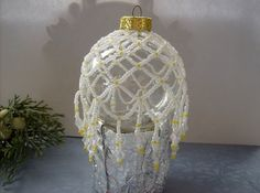 This removable white & yellow beaded ornament cover can be used on most glass ornaments to add a little holiday colour to your home!     Made with white lined seed beads, and yellow opaque seed beads, it adds a little bit of sunshine to the snow!    It is made with Netting stitch and drapes gracefully over your glass ornaments and be easily removed if the ornament itself gets broken!     Available in all colours and quantity orders are accepted!    *Glass ornament not included     $20.00
