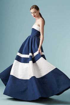 Raspberrily smiing milky-skinned ponytailed chocolette in strapless maxi gown w/ navy & snow bands of varying widths