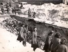 Bergen Belsen, Germany, Female SS guards standing near a mass grave, after liberation.