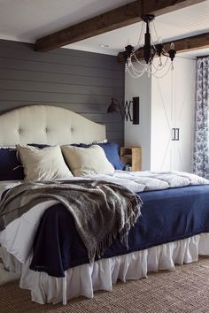 Add a hint of rustic, farmhouse authenticity to a bedroom with gray painted shiplap walls, a white ceiling and exposed wooden beams   Jenna Sue Designs