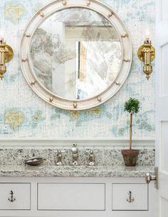 Modern porthole mirror in nautical bathroom with map wallpaper... http://www.completely-coastal.com/2016/09/decorative-bathroom-mirrors-coastal.html