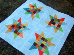 TUTORIAL: Spangle Quilt SPANGLE BABY QUILT  This scrappy baby quilt has a bold scale and plenty of eye appeal.  Use a charm pack or raid the scrap bin.  You will be happy with the results either way.