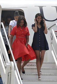 First Lady Michelle and daughters  Malia Obama in the front, Sasha Obama is behind her mom and Mrs. Robinson is emerging from the airplane.