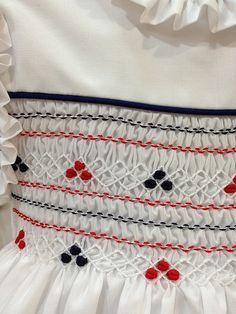 Vestido confeccionado en batista de algodón blanca con nido de abeja bordado totalmente a mano en tonos rojos y azul marino. Escote redondo con bies en marino, a juego con la sisa. Con combinación. Abotonado en la espalda con cinturón para poder ajustar el vestido al cuerpo de la niña. Un vestido clásico pero modernizado en tonos de verano y actuales. No te quedes sin él!! ARTESANÍA ESPAÑOLA (MADE IN SPAIN)