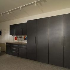 Garage cabinets all down the longest wall with counter running down the right wall side