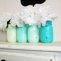 Painted mason jars in different shades with white flowers for decor on shelf or mantel.