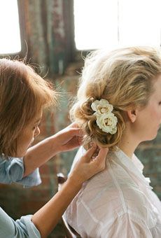 Wavy, side bun bridal hairstyle with flower accessories