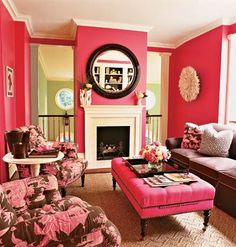 Dark pink sitting room with brown sofa, tufted ottoman, and a dramatic focal point in the fireplace.