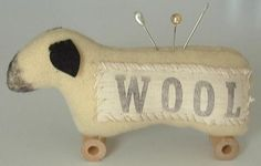 """Sheep pin cushion  Handstitched from felted, hand-dyed wool with stamped muslin and vintage spools (pins may vary).  4"""" x 5"""""""