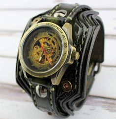 2015 DESIGN from CUCKOO NEST ART STUDIO Mens army green color watch cuff made with veg tanned leather, completely handmade, hand tooled, hand stitched with natural thread. The leather cuff is 2 1/2 inches wide. Item includes a mechanical skeleton watch face and is removable and