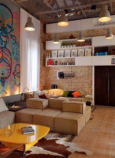 Нравится кирпичная кладка, белые полки, деревянный пол, промышленные светильники, модульная мягкая мебель