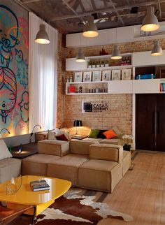 Techo industrial expuesto, pared de ladrillo crudo, estantería a doble altura, graff vandal en la pared y piso de madera... Brutal! Combinación impecable. Solo sobra la alfombra de vaca, digo.