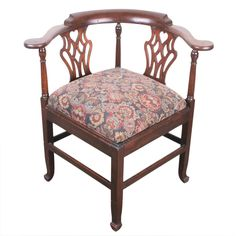 """An antique mahogany corner chair in the English Chippendale style that showcases a rounded back, mirrored carved designs with a heart motif. The drop seat is upholstered in a floral motif. Seat: 19"""" ("""