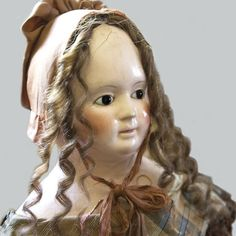 What a beautiful lady with such a serene face. Long human hair curls fall to her shoulders! A beautiful doll!