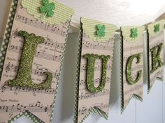 "St. Patrick's Day ""Lucky"" Banner - A green & cream polka dot paper is the bottom layer of the banner with sheet music as the backdrop for the green glittered letters spelling ""Lucky"". A sweet scallop detail is at the top of the pennant with a shamrock in the center."