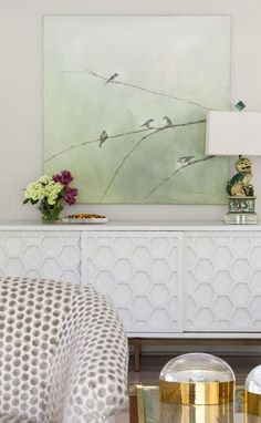 White honeycomb credenza with a Foo dog lamp features brass legs against white walls displaying a green wall art with birds on branches.