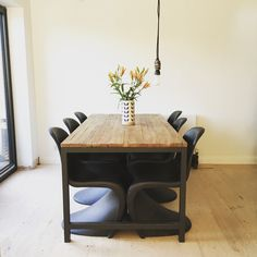 Dining/Kitchen space. Minimal decoration. Plumen bulb and Verner Panton chairs in black.
