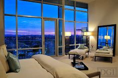 This bedroom uses soothing neutrals and warm minimalism to provide a restful, relaxing environment. The soft colors and fabrics allow one to focus on the incredible view of surrounding Nashville. The famous Tennessee hills are picturesque at sunset, as seen here, and are a welcome sight with which to start the morning. Nashville penthouse design by Dana Goodman Interiors. www.DanaGoodmanIn... #InteriorDesign #Interior #Design #Designer #Nashville #Citylife
