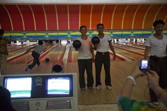 Two North Korean men have their photo taken by a relative after finishing games of bowling at a Pyongyang, North Korea bowling alley on Friday September 7, 2012.