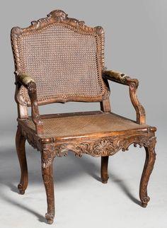 """Trabajo francés, primera mitad del S. XVIII. Sillón de brazos """"a la reina"""" de madera de nogal, con decoración tallada, Medidas: 100 x 47 x 63 cms."""