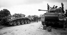 Waffen SS soldiers inspect wrecked Allied tanks