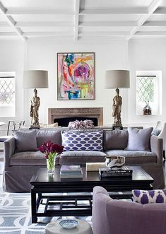 Colorful abstract artwork, purple ikat pillows, Asian figurine lamps, Chippendale coffee table, lavender velvet
