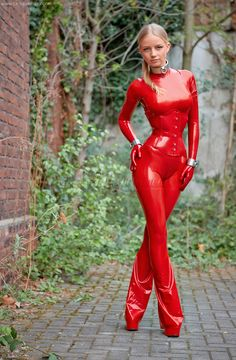 Girl in red latex with wearing things on hands and legs to tie on and put her in bondage
