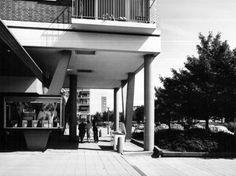 Datering tot: 1975-12-31 Beschrijving: Het winkelcentrum aan de Mgr. Nolenslaan gezien in de richting van de R.K. St. Johannes de Doperkerk.