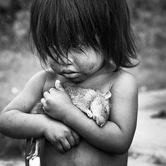 Niña guaraní abraza con fuerza a una rata muerta.