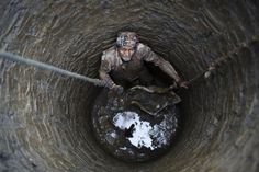 A man looked up at his friends, unseen, as they removed mud from the construction site of a well in Khokana, Nepal, Monday. (Navesh Chitrakar/Reuters)