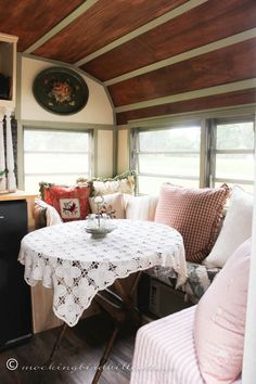 A wood paneled ceiling adds a degree of comfort and the fold up table lends flexibility to this campers design.
