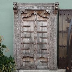Antique Indian Door with surround Circa 1900.  Beautiful old artisan carved teak wood with intricate carved wood detail through out.  Decorative carved frame and border.  Finished in a sun bleached wood.  We offer professional installation services if you are interested in replacing your existing doors or garden gates with our one of a kind antique doors. Available in Los Angeles at  MIXfurniture.com