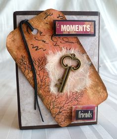 Key Moment Art Block -made with scap wood that is sanded and stained and then paper added to all sides, this on has an embellishment of a tag I made using Tim Holtz ink and stamped over, added mulberry paper, key and 3 dimensional word tiles.