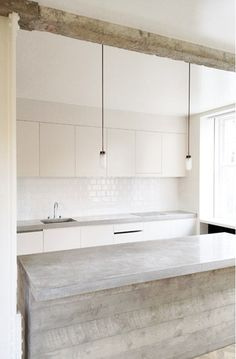 pale shades of nature in modern rustic kitchen, driftwood, concrete counter, white tile, wood beam, all in shades of white, grey, & cream