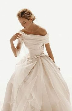 Classical wedding dress with excessive fabric folding into such a beautiful way. The off shoulder really adds character and elegance. The nipped in waist and fuller skirt work perfectly together. Beautiful.