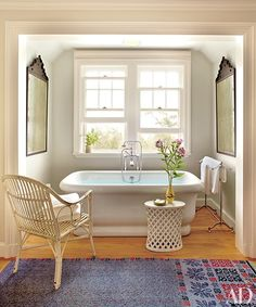 Moroccan mirrors from Downtown flank a Waterworks tub in the master bath; the tub fittings and towels are also by Waterworks, the side table is by Paul Mathieu for Stephanie Odegard Collection, and the towel stand is by RH