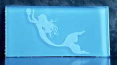 Glass subway tile with etched mermaid with pearl