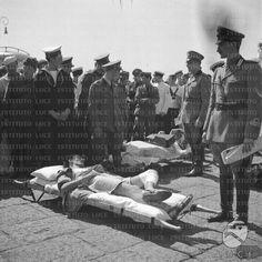 Ufficiali, marinai e soldati assistono due feriti in barella sul molo del porto dove sono stati sbarcati  RG/RG099/RG00003665.JPG