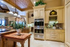 A spacious contemporary country kitchen in cream and hardwood in warm tones. The L-shape of the kitchen includes ample work space that looks over the adjacent dining room and a small desk workstation with a matching backsplash. Above the small countertop next to the double oven is a plate rack and a small decorative cubby that houses an urn with a peach motif.