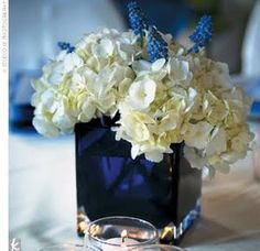 Short cobalt blue vases packed with ivory hydrangeas alternated with taller arrangements.