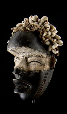 Africa | 'House / passport' mask from the Dan people | Wood, pigment, cowrie shells, plant fiber